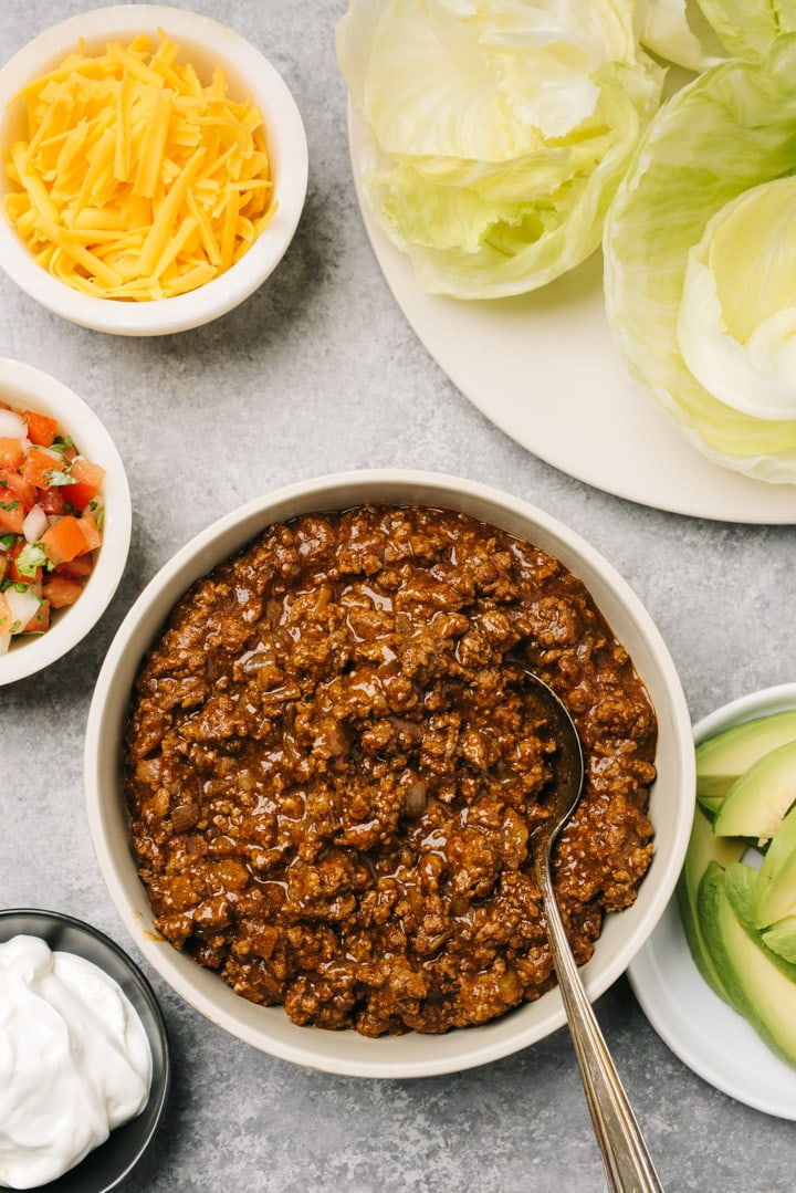 A bowl of keto ground beef taco meat surrounded by various low carb toppings on a cement background.