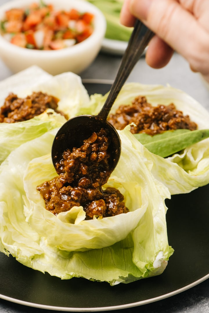Keto ground beef taco meat being portioned into an iceberg lettuce shell.