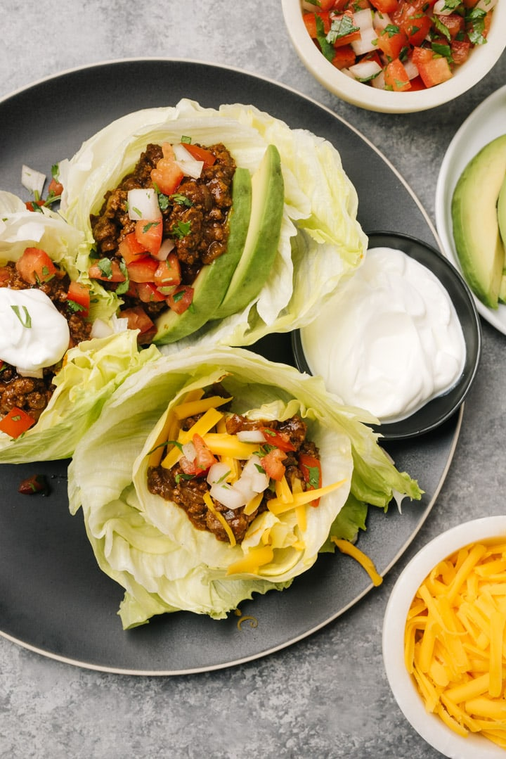 Three keto tacos with ground beef filling, iceberg shells, and various low carb tacos on a black plate.