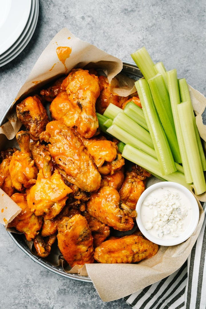 A platter of instant pot buffalo chicken wings with celery sticks and blue cheese dressing on a cement background.