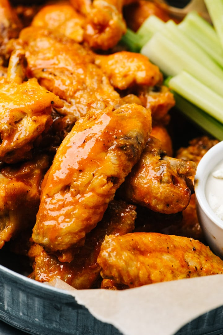 Side view, a platter of instant pot chicken wings with celery sticks and blue cheese dipping sauce.