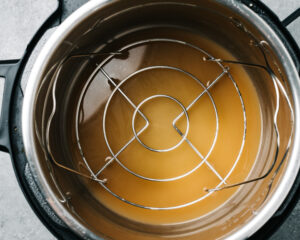 Chicken broth in an an instant pot with a trivet nested inside.
