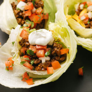Side view, three ground beef keto tacos in iceberg lettuce shells topped with sour cream, avocado, and pico de gallo.