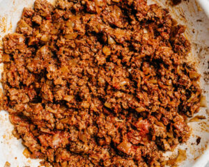 Cooked ground beef with onions, tomato paste, and taco seasoning in skillet.