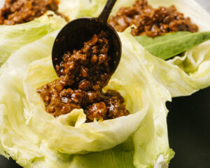 A spoon scooping keto ground beef taco meat into an iceberg lettuce shell.