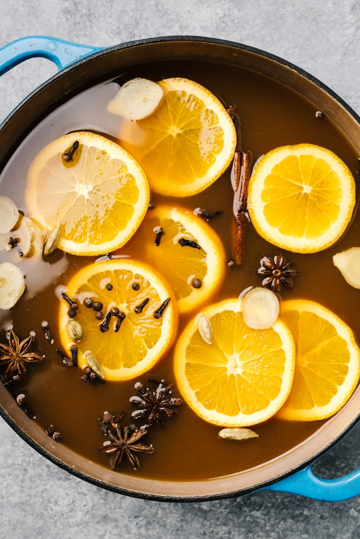 The ingredients for mulled apple cider combined in a blue dutch oven.