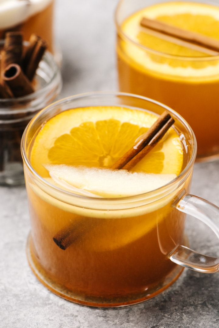 Three glasses of mulled cider with whiskey on a cement background, each garnished with oranges, apples, and a cinnamon stick.