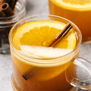 Two mugs of mulled apple cider garnished with an orange slice, apple slice, and cinnamon stick on a cement background.