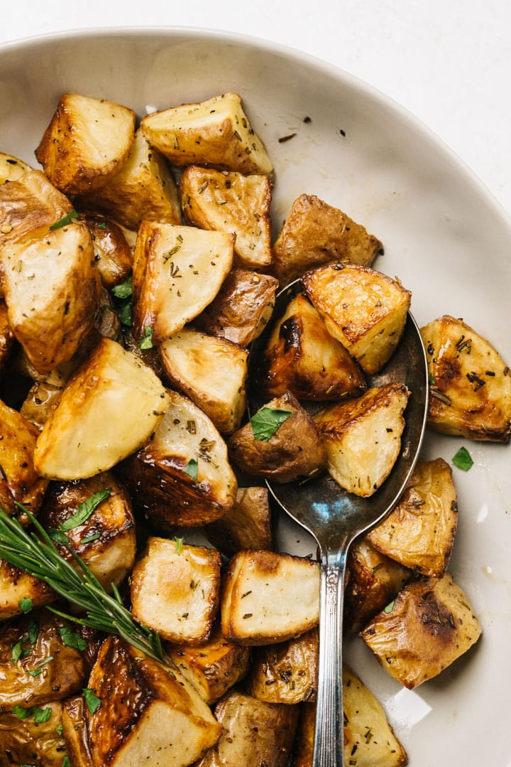 A tan serving bowl of rosemary roasted potatoes with a vintage serving spoon.
