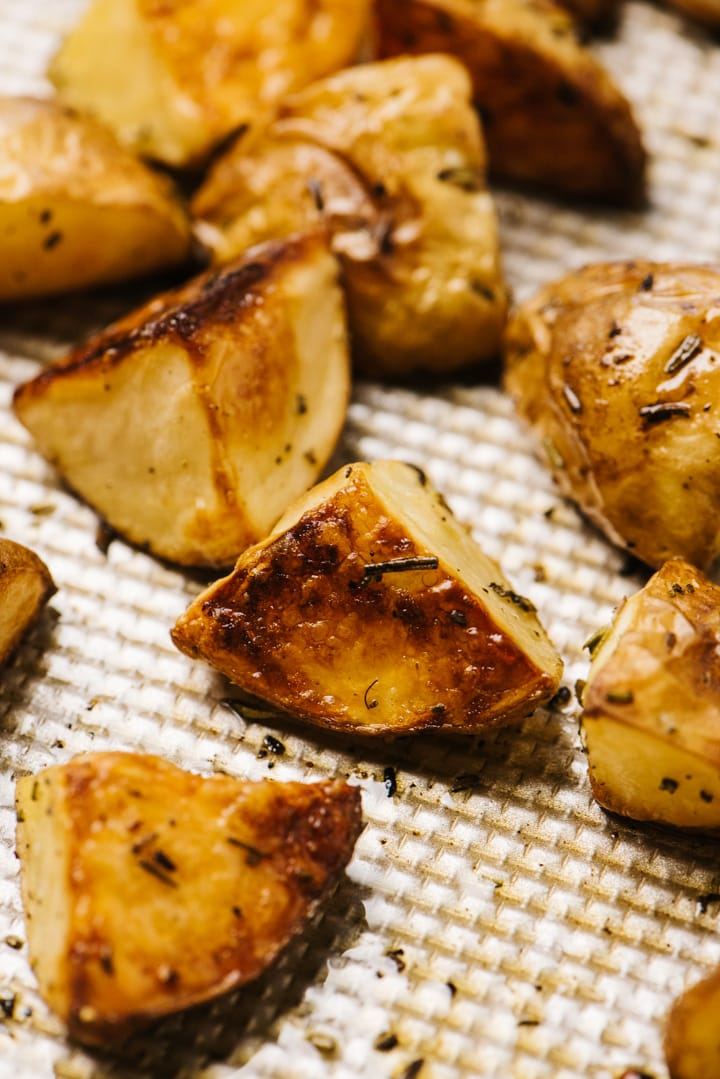 Side view, rosemary roasted potatoes on a baking sheet.