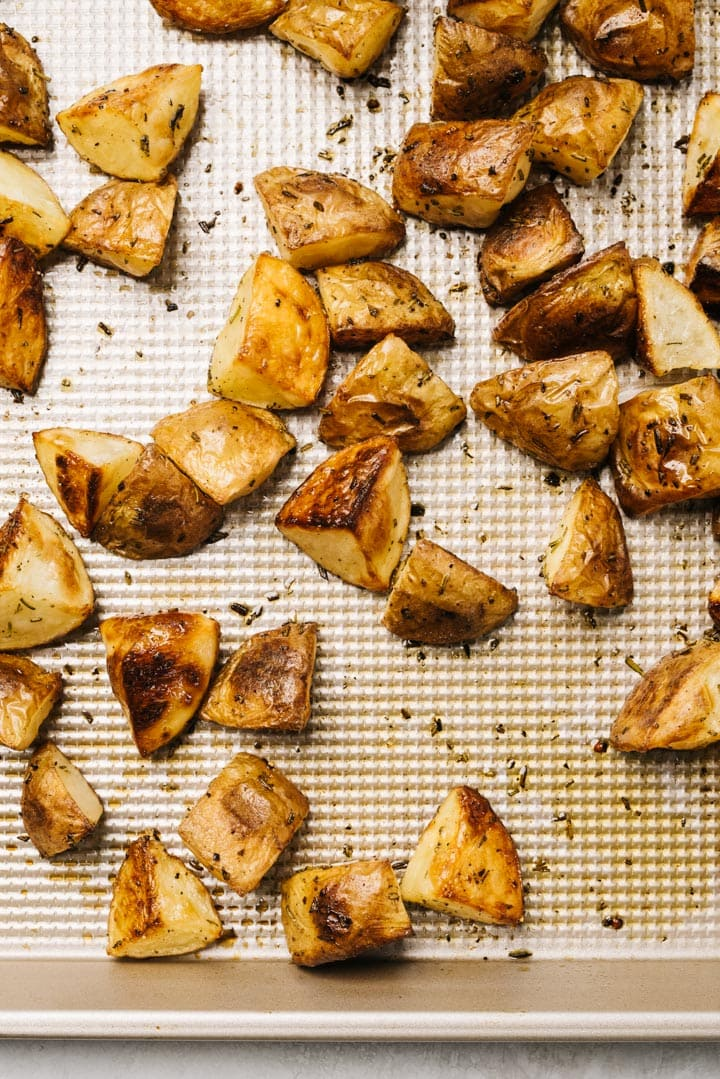 Roasted potatoes with rosemary on a baking sheet.
