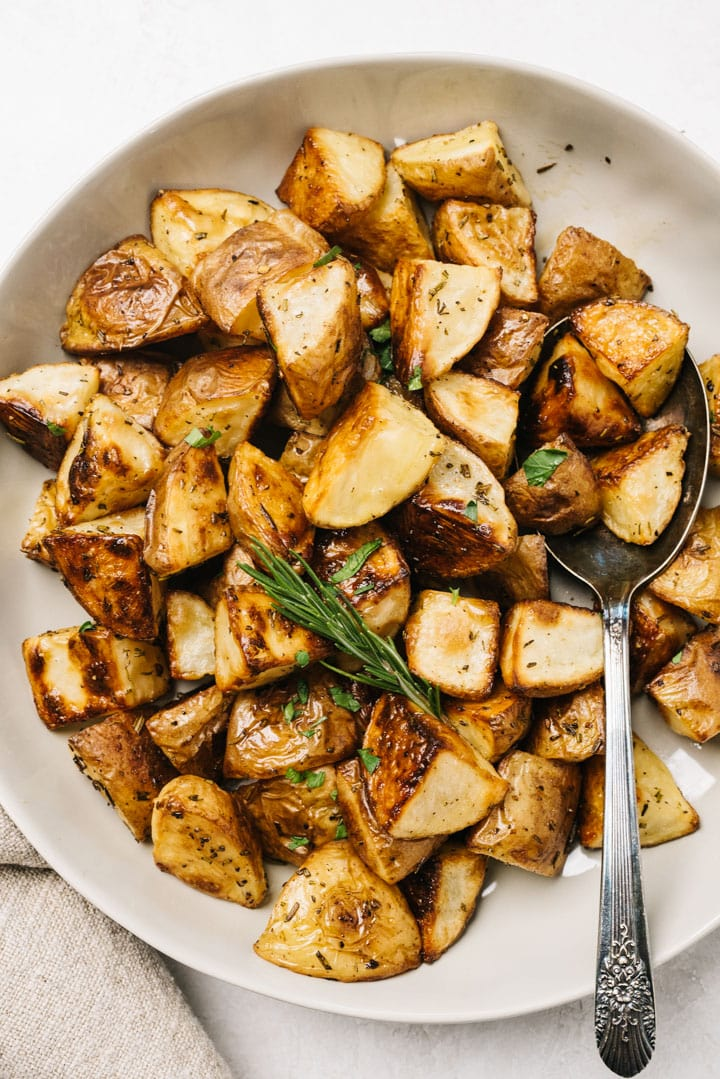 A bowl of crispy rosemary roasted potatoes in a serving bowl with a serving spoon and sprig of fresh rosemary.