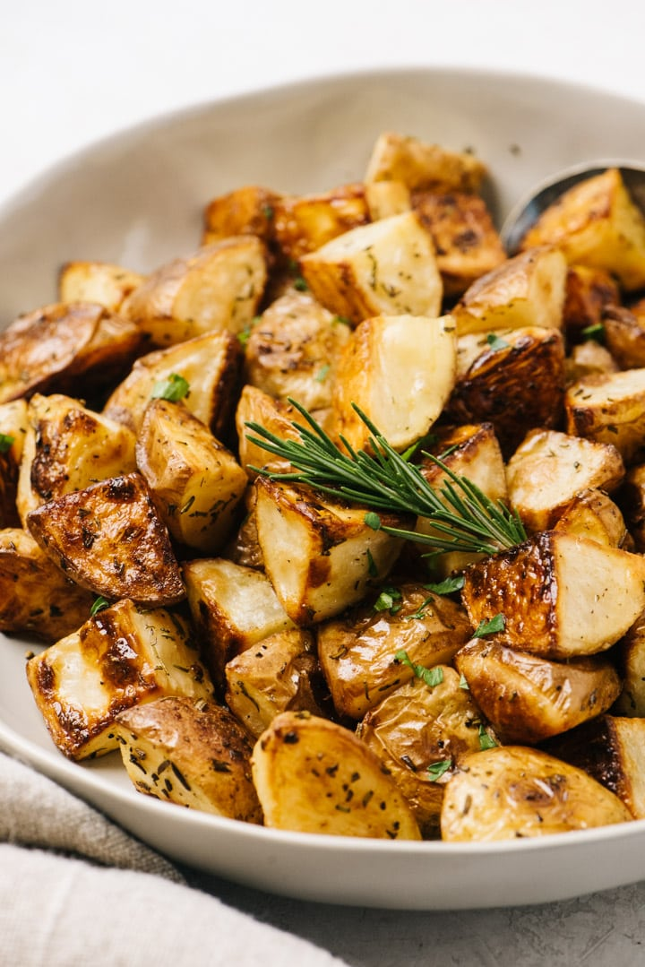 Side view, extra crispy roasted potatoes with rosemary in a tan serving bowl.