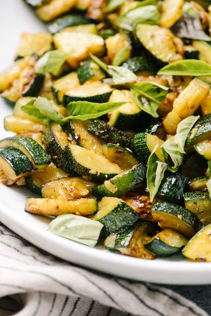 Side view of a bowl of sautéed zucchini garnished with fresh basil.