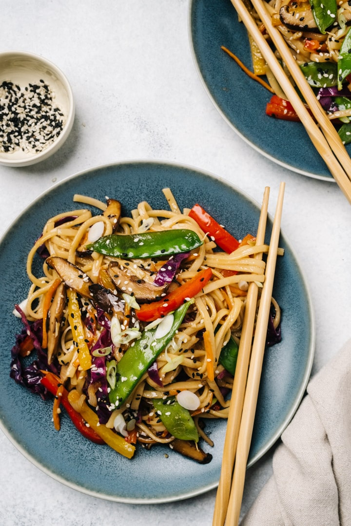Two servings of vegan stir fry noodles on blue plates with wood chopsticks on a cement background.