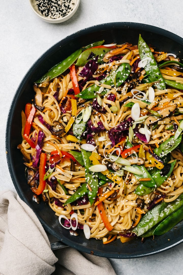 Stir fry with noodles and vegetables in a skillet on a cement background with a small bowl of sesame seeds.
