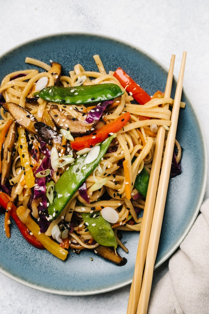 A serving of stir fry noodles with rainbow vegetables on a blue plate with wood chopsticks and a tan linen napkin.