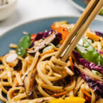 Side view, chopsticks twirling stir fry noodles with rainbow vegetables.