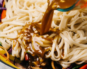 Pouring stir fry sauce over noodles and vegetables in a skillet.