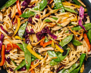Stir fry noodles with rainbow vegetables in a skillet.