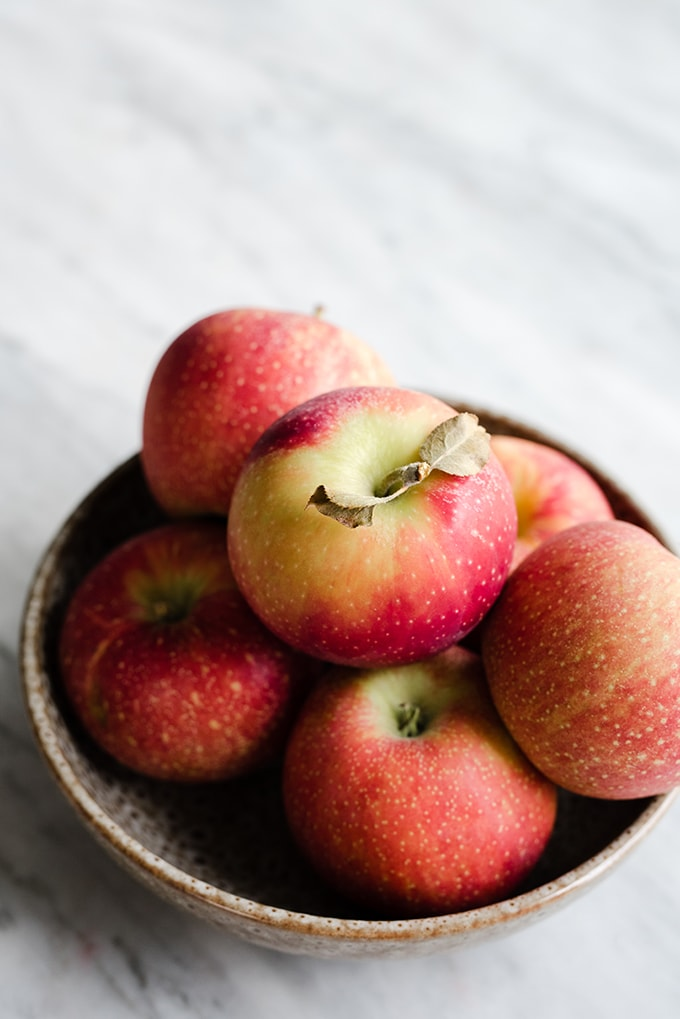 Freshly picked apples in a ceramic bowl on a marble table.