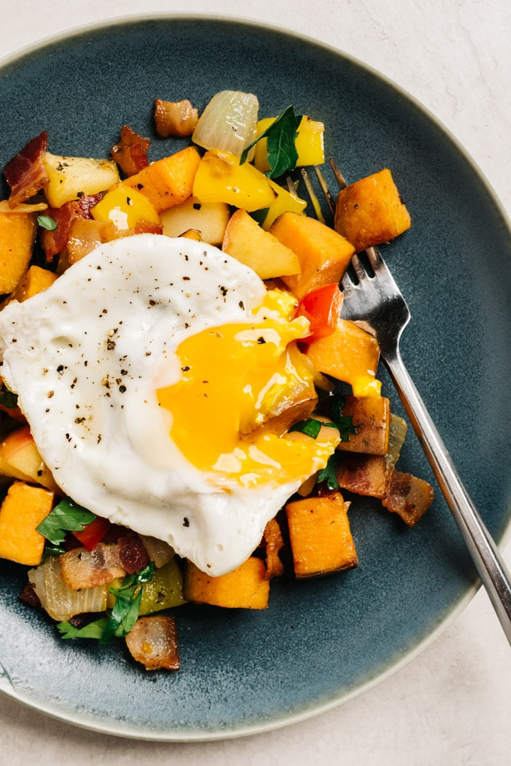 A fried egg with a broken, runny yolk over bacon sweet potato hash on a blue plate with a silver fork.
