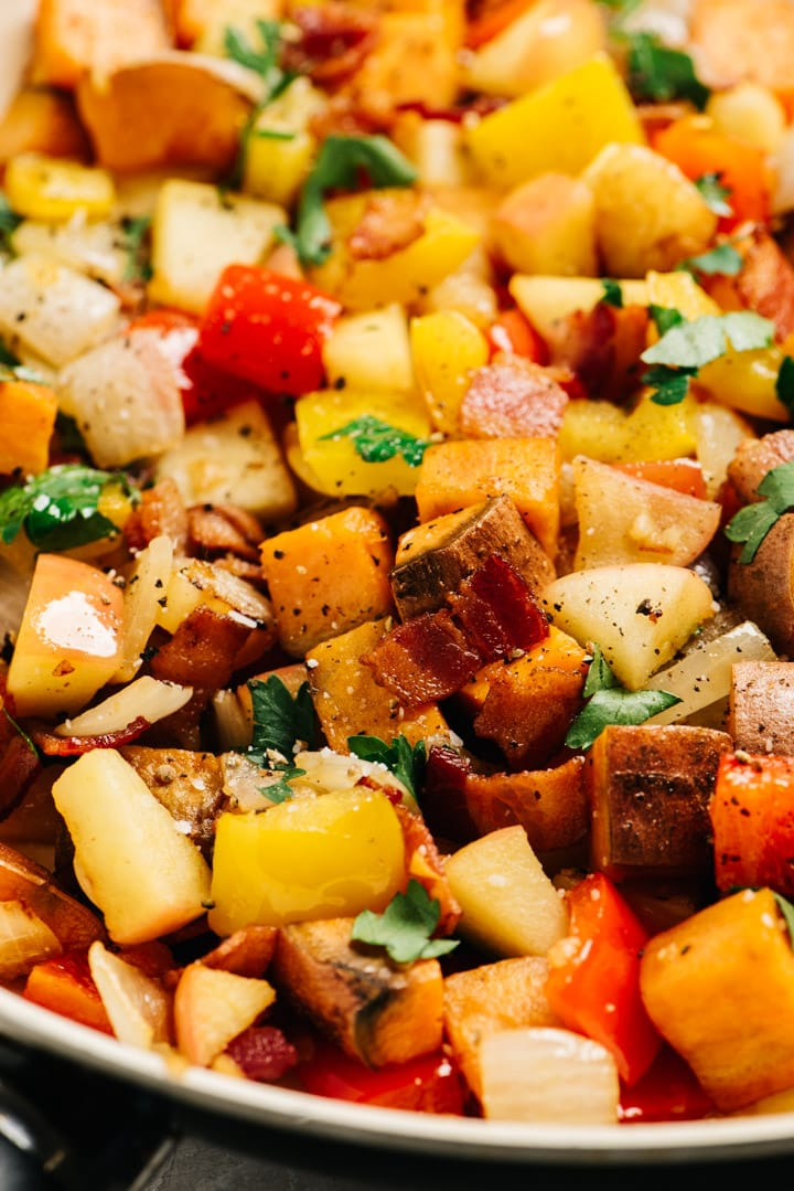 Side view, sweet potato hash with bacon and apples in a skillet.