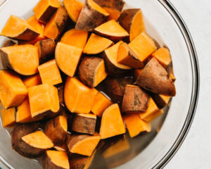 Par-cooked diced sweet potatoes in a glass bowl.