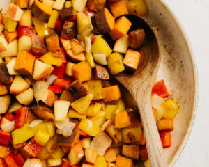 Sautéed sweet potatoes, onions, bell peppers, and apples in a skillet with a wood spoon.