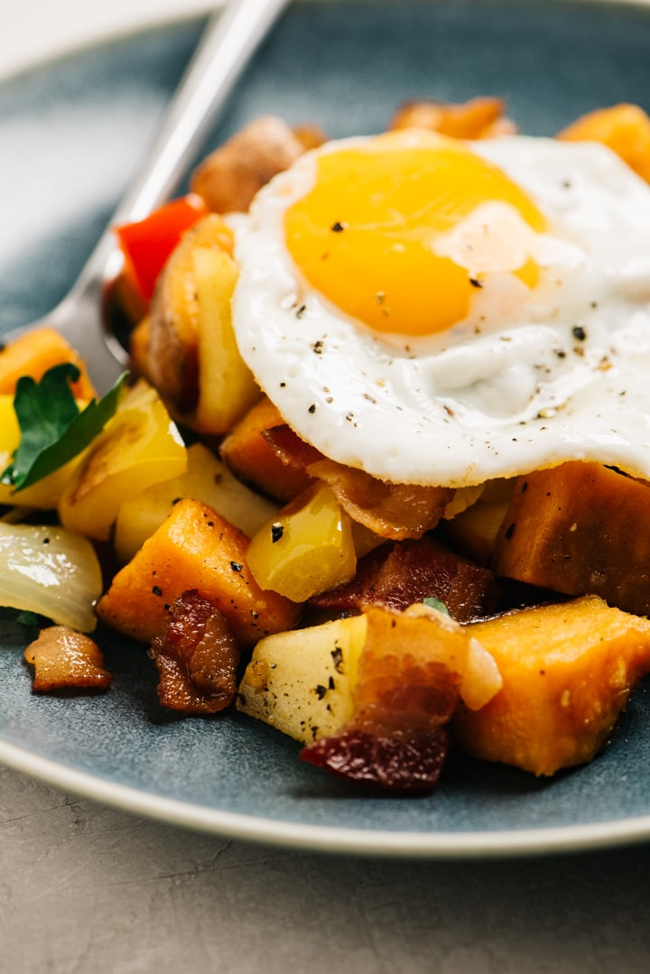 Side view, bacon sweet potato hash on a blue plate topped with a fried egg.
