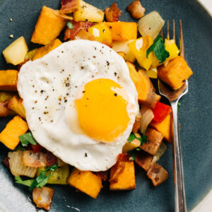A fried egg served over sweet potato hash with bacon and apples on a blue plate with a silver fork.