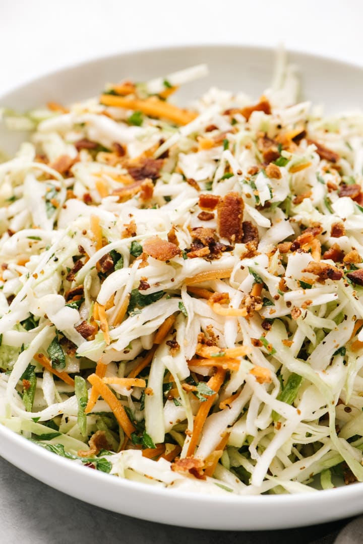 Side view, keto coleslaw with bacon vinaigrette in a white serving bowl.