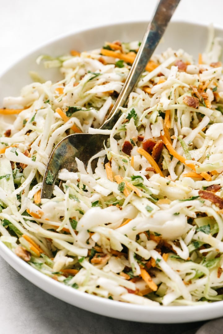 Side view, keto and whole30 bacon coleslaw in a white serving bowl with a silver serving fork.