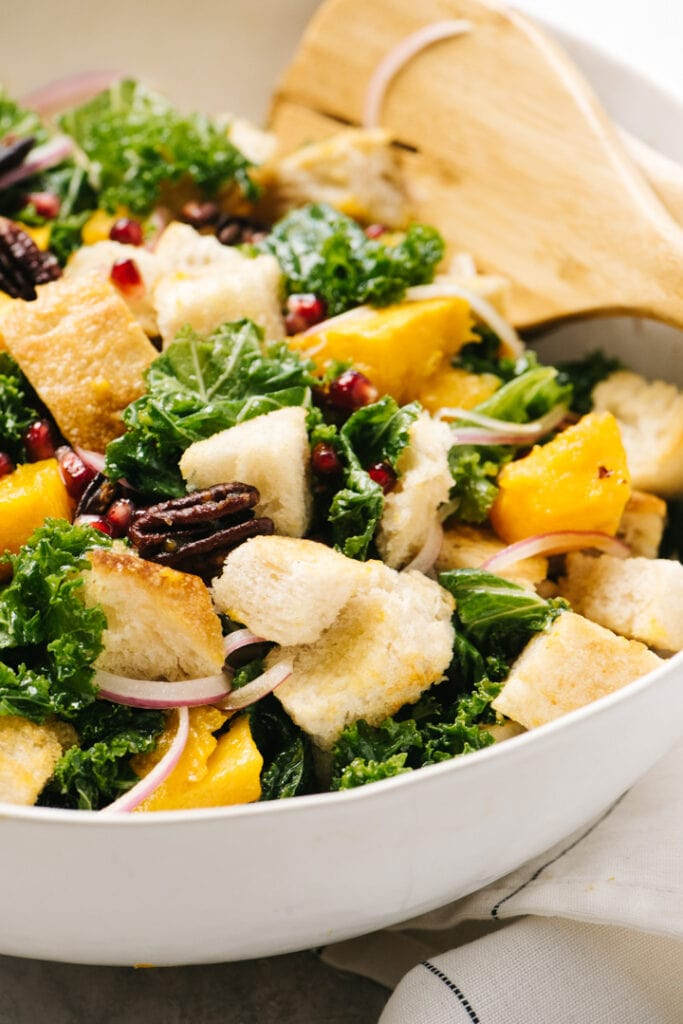 Side view, butternut squash panzanella in a large white salad bowl with wood serving utensils.