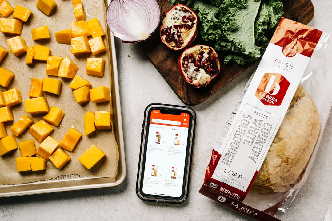 The ingredients for butternut squash panzanella arranged on a cement background with a phone open to a grocery store app.