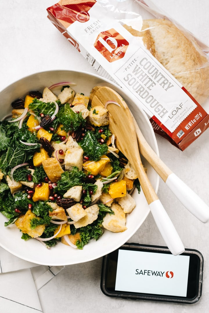 A bowl of butternut squash panzanella with a load of sourdough bread and an phone with the Safeway app.