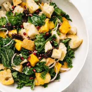 A white salad bowl filled with butternut squash panzanella salad.