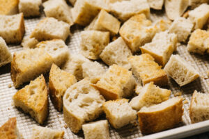 Toasted sourdough bread pieces on a baking sheet.