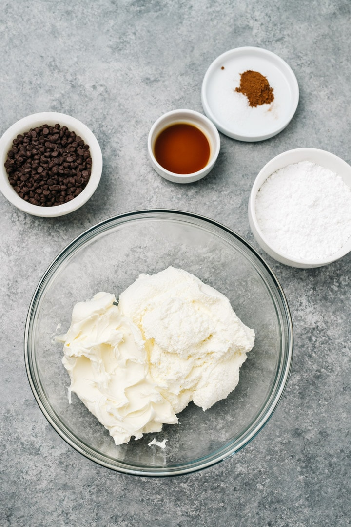 The ingredients for cannoli dip arranged on a cement background.