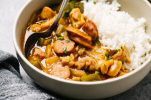 Side view, chicken étouffée in a tan bowl served over white rice with a dark grey linen napkin.