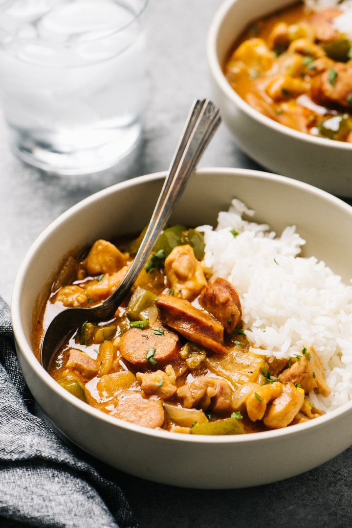 Side view, two bowls of étouffée made with chicken and served over white rice on a cement background.