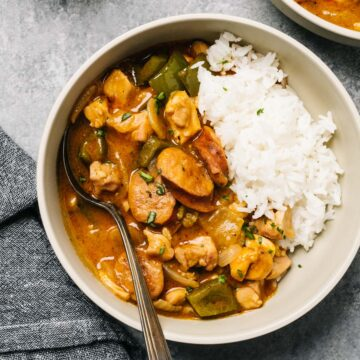 A bowl of chicken étouffée served over white rice on a cement background.