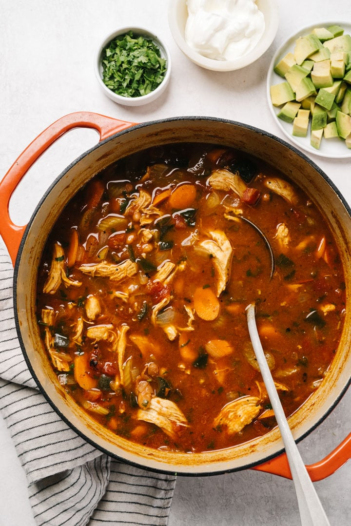 Cooked chicken taco soup in a dutch oven with a metal ladle surrounded by bowls of various toppings.