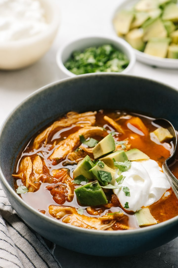Side view, a bowl of chicken taco soup on a cement background surrounded by small bowls of garnishes and toppings.