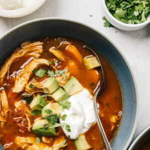 A bowl of chicken taco soup garnished with sour cream, diced avocado, and cilantro.