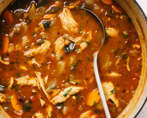 Cooked chicken taco soup in a dutch oven with a metal ladle.