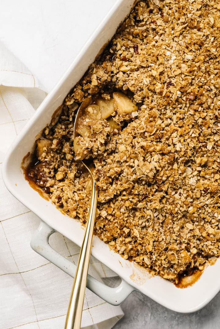 A serving spoon dipped into gluten free apple crisp with a white and gold linen on the side.
