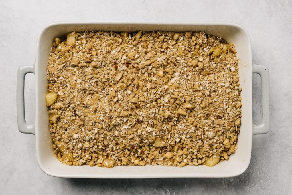 Apple crisp with gluten free topping n a casserole being being baked.