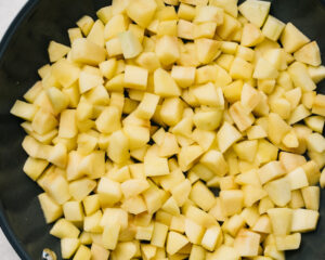 Sauteed apples in a skillet; pouring sweetener, seasonings, and thickener into apple crisp filling.
