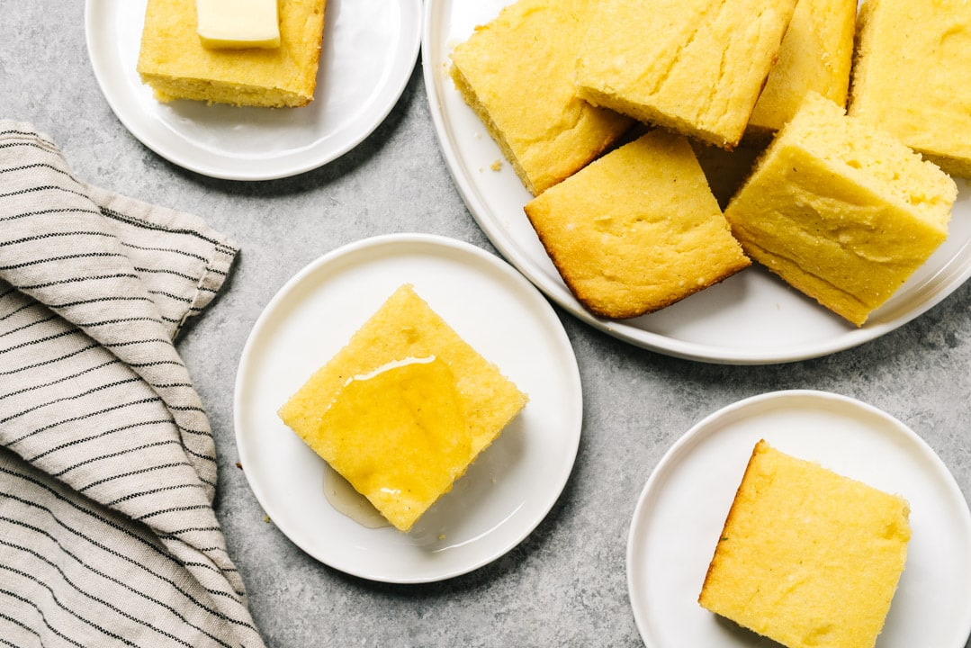 Several pieces of healthy cornbread on a small plates next to a platter and a tan striped napkin.